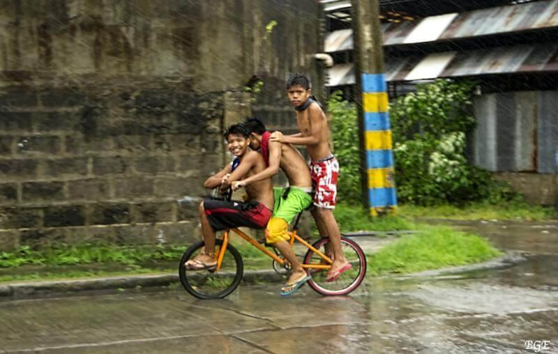 Мальчишки едут на велосипедах под проливным дождем на Филиппинах